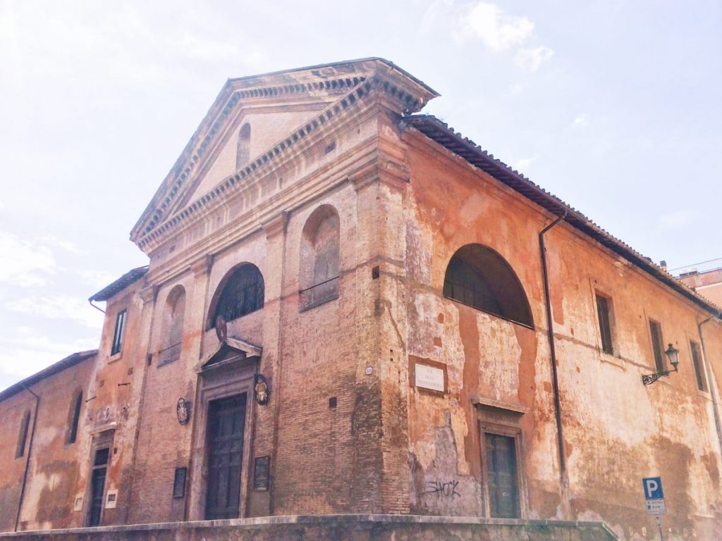 Façade and exterior of the chiesa di San Giovanni Decollato on the right; entrance to the complex of San Giovanni Decollato on the left, Rome