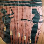 "Simulation of a loom with a series of weights hanging from the warp threads in order to stretch the weaving, second room of Mundus muliebris, Museo Civico Archeologico ""Lavinium"", Pomezia (RM)"