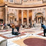 The staff cleaning off the red rose petals fallen on the floor of the monument, after the Pentecost ceremony at the Pantheon in Rome
