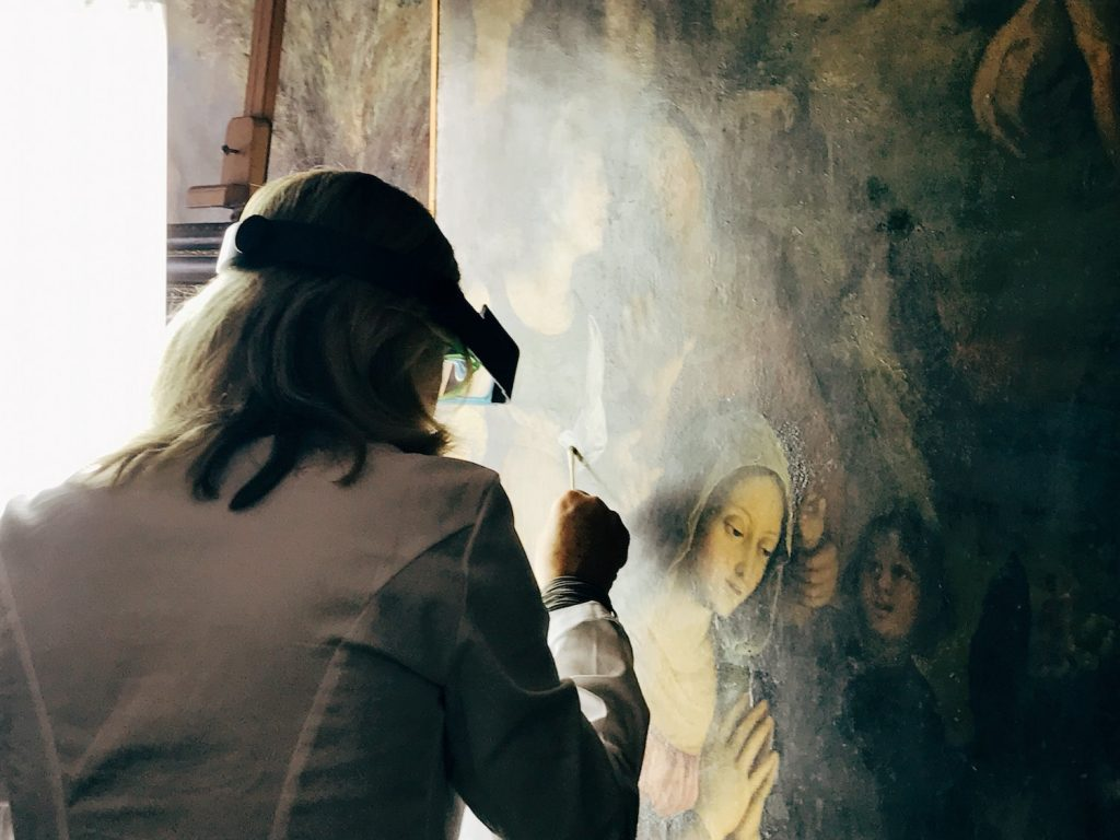 Restorer Valeria carrying out a proof to remove the yellowish aged varnish from a painting surface at the restoration laboratory, Rome