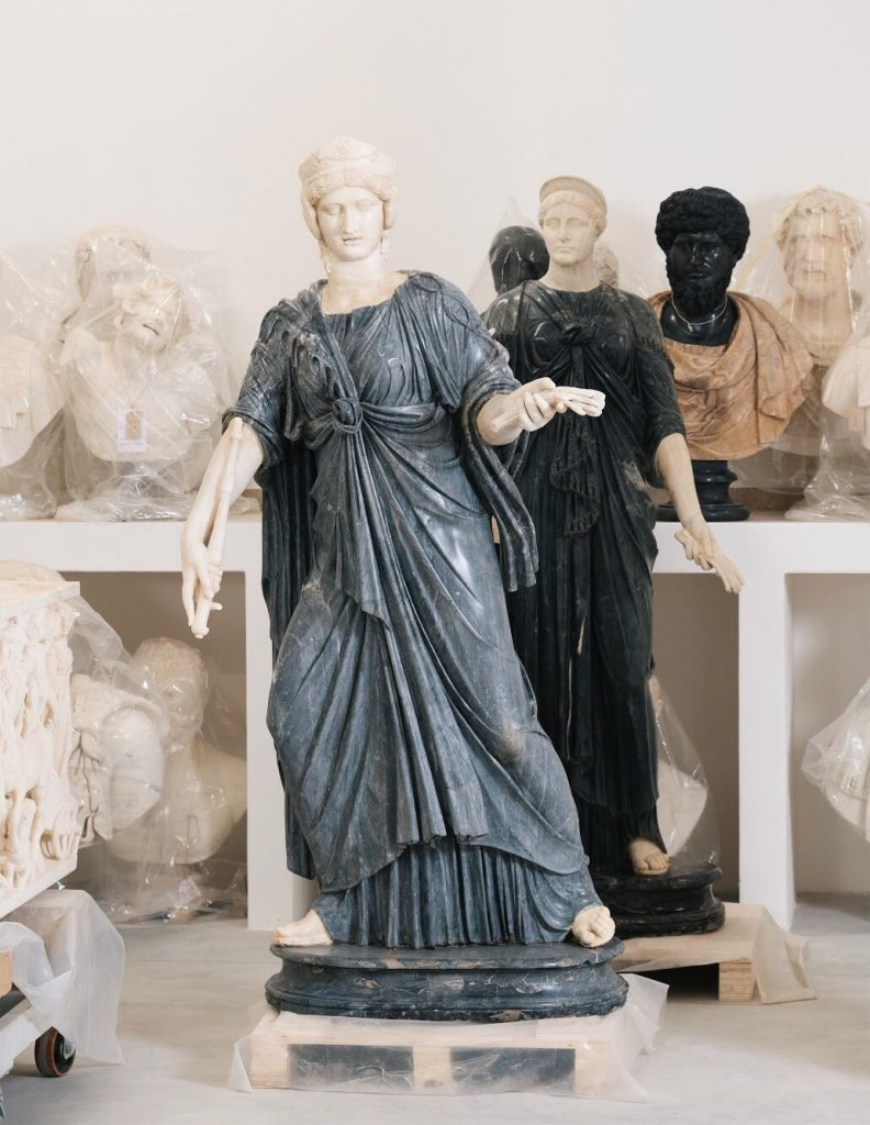 Group of restored sculptures: in the foreground two statues of Isis made of bigio morato marble (Inv. 032 and 031) and in the background busts of emperors and bust of drunken Satyr (Inv. 111), Collezione Torlonia, Via della Lungara, ©FondazioneTorlonia, Ph. Lorenzo De Masi